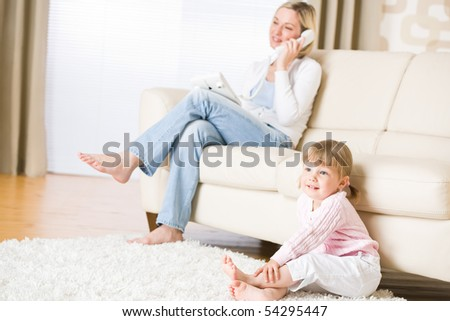 Mother and child in living room watch television, mother on phone in background on sofa
