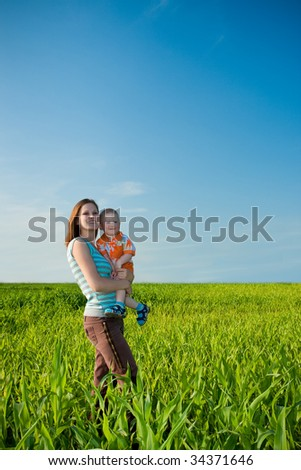 mother and child in the green field - stock photo