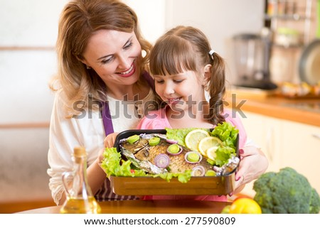 mother and child jolly look at prepared dish of fish in kitchen - stock photo
