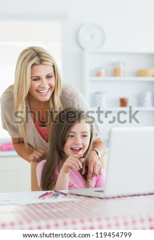 Mother and child laughing at laptop with child pointing in the kitchen