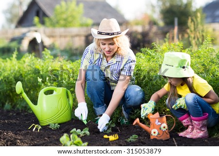 mother and child little daughter planting vegetable in home garden field - stock photo