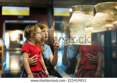 mother and child looking ancient amphores in  museum