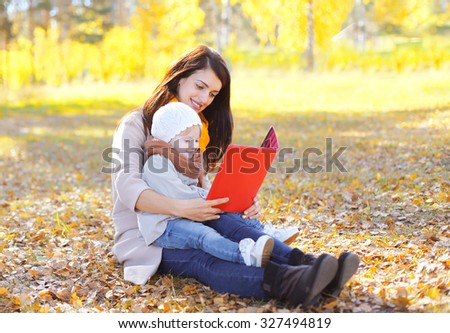 Mother and child looking on book or tablet pc sits together on leaves in autumn park