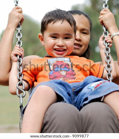 Mother and child on a swing - stock photo
