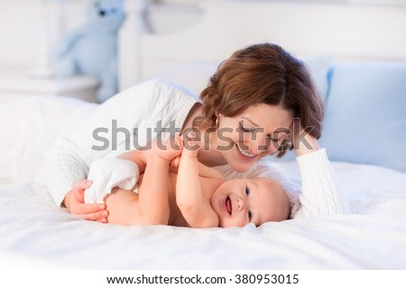 Mother and child on a white bed. Mom and baby boy in diaper playing in sunny bedroom. Parent and little kid relaxing at home. Family having fun together. Bedding and textile for infant nursery. - stock photo