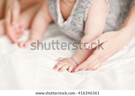 Mother and child on a white bed. Mom and baby girl in home dresses in sunny bedroom. Parent and little kid relaxing at home. Family having fun together. Bedding and textile for infant nursery. - stock photo