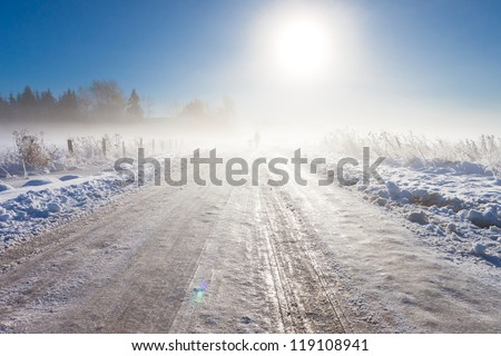 Mother and child on foggy snow road near farm - stock photo