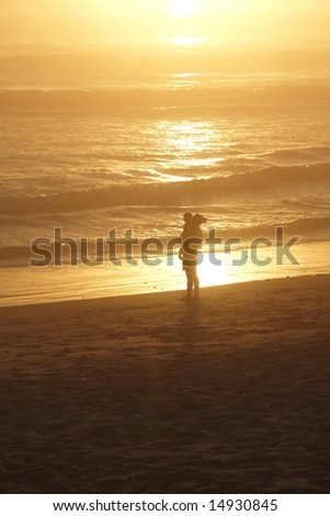 Mother and child on the beach at sunset with orange background