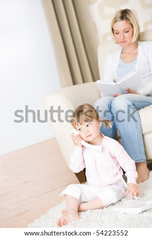 Mother and child - on the phone in living room with book