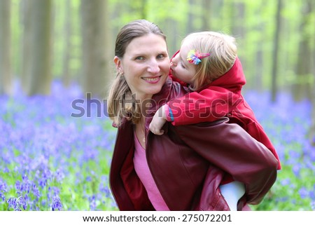 Mother and child outdoors playing, kissing and hugging. Happy family of two, young smiling woman and her cute toddler daughter enjoying beautiful day in the forest with bluebells flowers - stock photo
