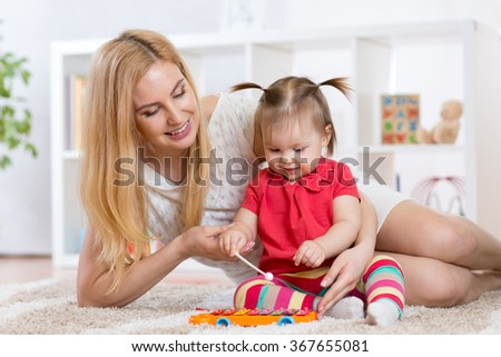 mother and child play instrument - stock photo