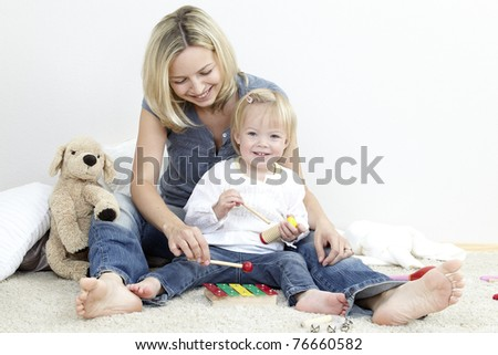 mother and child play instruments - stock photo