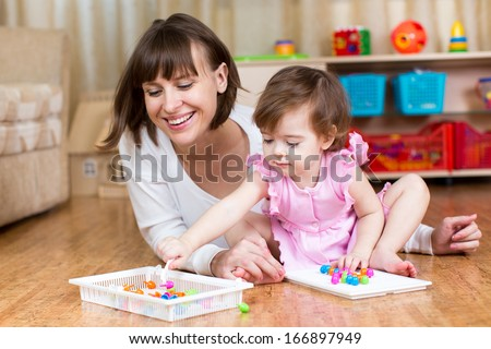 mother and child play mosaic toy together indoors - stock photo