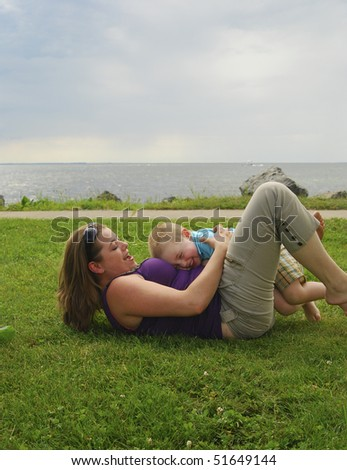 Mother and child playing on beach focus on child. - stock photo