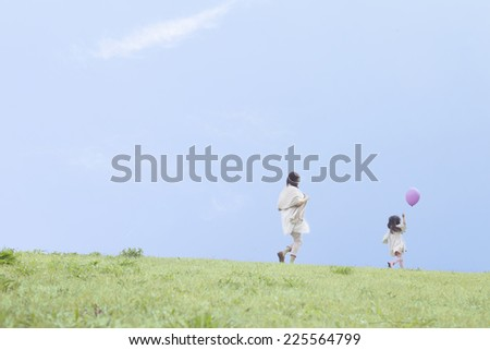 Mother and child playing on the grass - stock photo