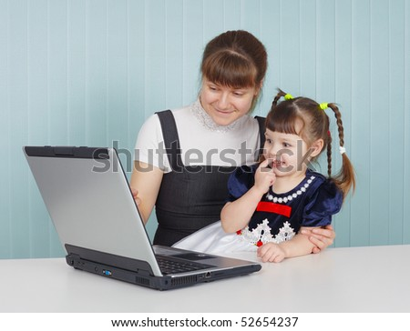 Mother and child playing with a laptop at the table