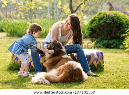 mother and child playing with dog on nature. outdoor about sander - stock photo