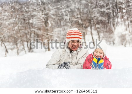 Mother and child playing with snow - stock photo
