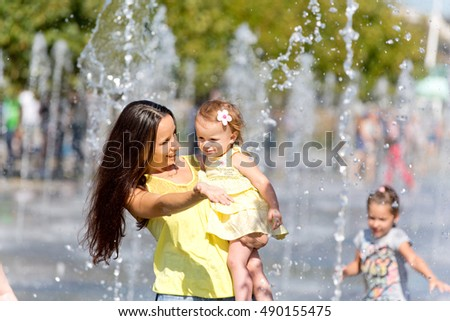 Mother and child playing with water jets of the fountain on a hot summer day