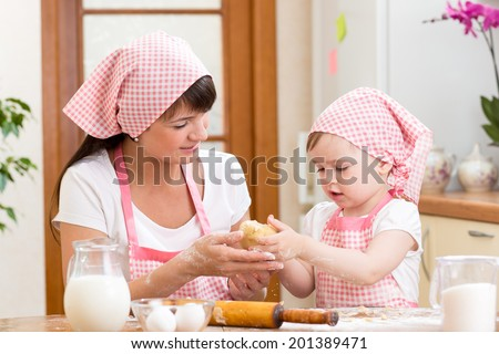 Mother and child prepare cookies at kitchen - stock photo