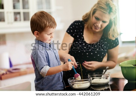 Mother and child preparing cookies in kitchen - stock photo