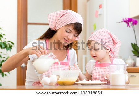 Mother and child preparing cookies together at kitchen - stock photo