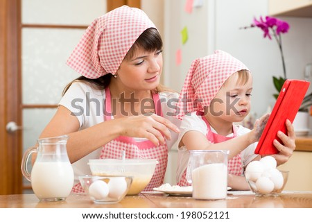 Mother and child preparing pastry together at kitchen and looking at cookbook - stock photo
