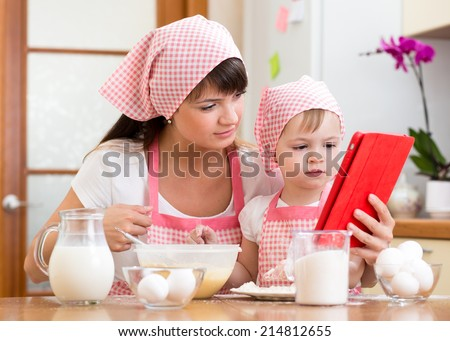 Mother and child preparing pastry together at kitchen and looking at tablet for recipe - stock photo