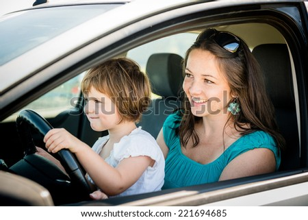 Mother and child pretend driving car sitting both on front driver seat - stock photo