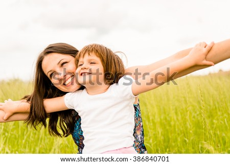 Mother and child pretend with hands they are together flying - stock photo