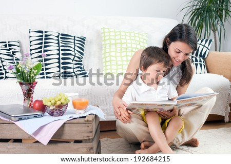 Mother and child, reading a book and eating fruits - stock photo