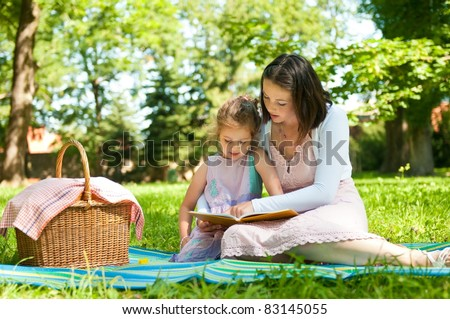 Mother and child reading book on picnic in park - stock photo
