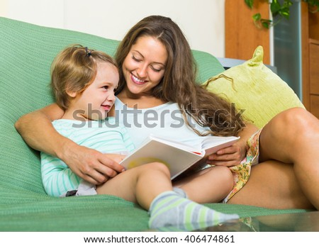 Mother and child reading book together on couch in home. Focus on woman - stock photo