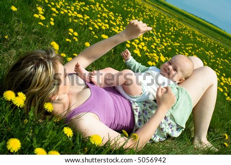 Mother and child relax and play in a field of yellow flowers - stock photo