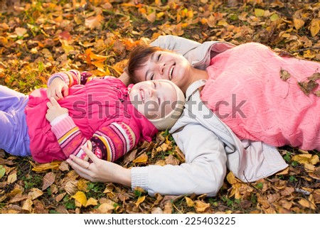 mother and child relax laying on autumnal leaves outdoors - stock photo