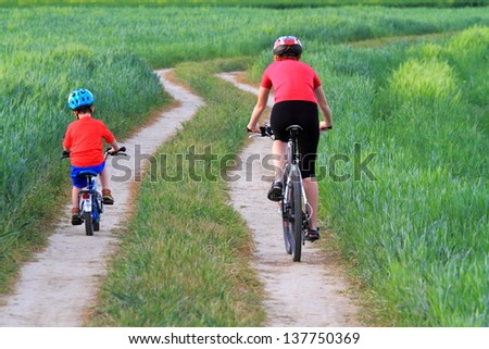 Mother and child riding bikes together during summer - stock photo
