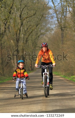 Mother and child riding bikes together in the wood during springtime - stock photo