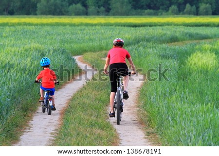 Mother and child riding bikes together on a green field - stock photo