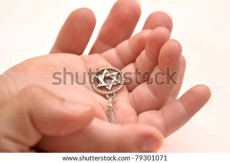 Mother and child's hands holding silver star of David - stock photo