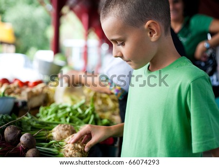 Mother and child shopping at farmer's market for fruits and vegetables