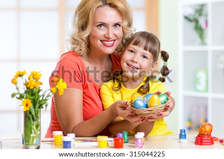 Mother and child showing painted  Easter eggs at home interior - stock photo
