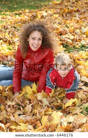 mother and child sit among fallen leaves