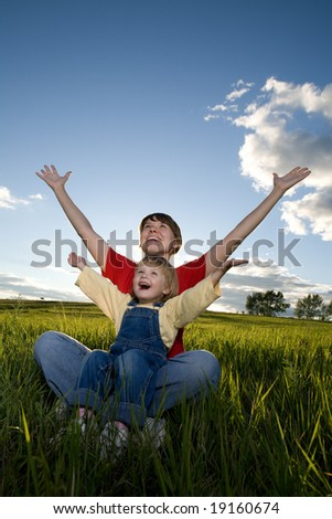 mother and child sit in field and hands up - stock photo