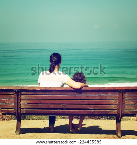 mother and child sitting on bench and looking forward at the sea