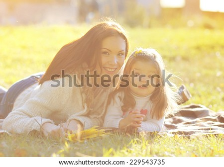 Mother and child smiling having fun in sunny autumn day - stock photo