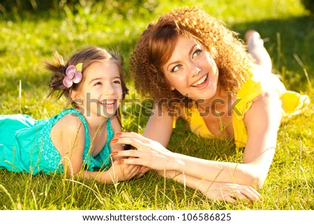 mother and child smiling in the park on a sunny day - stock photo