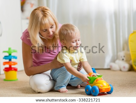 Mother and child son playing with toy car on nursery floor - stock photo