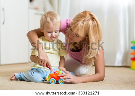 mother and child son playing with toy cars on floor at home - stock photo