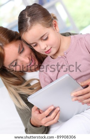 Mother and child using electronic tablet at home - stock photo