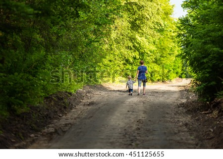 Mother and child walking by forest path with holding hands. Summer forest and family.